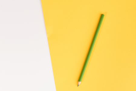 Green pencil on color paper background