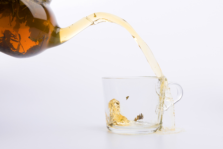 Splash in glass cup of green tea isolated on white background
