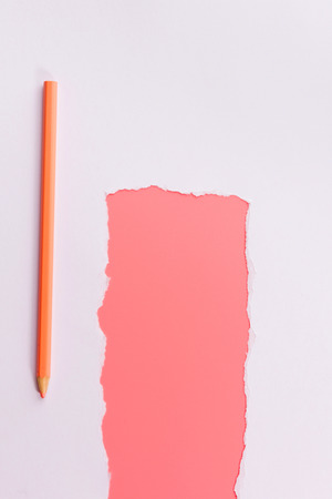 White torn paper over pink background with pencil 写真素材