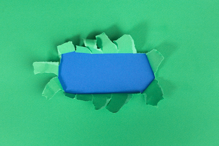 green torned paper over blue background 写真素材 - 121673285