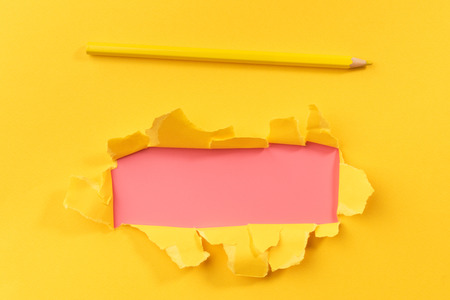 Yellow torned paper over pink background with pencil
