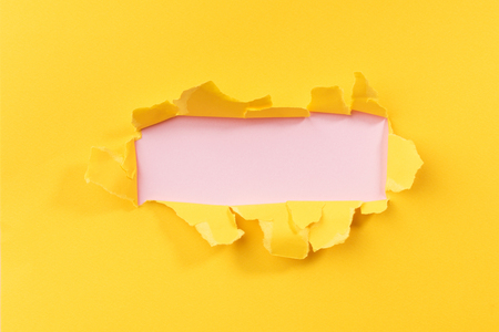 Yellow torned paper over pink background Imagens