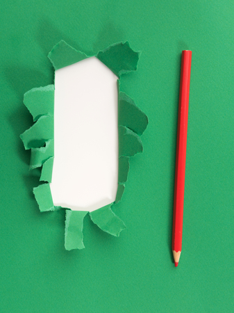Green torned paper over white background with pencil