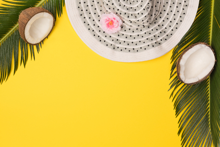 hat, coconuts and palm leaves isolated on yellow background, top view