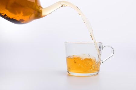 Théière en verre verser le thé vert dans la tasse isolé sur fond blanc