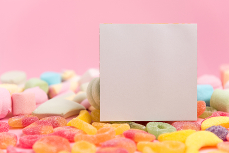 Sweets and a blank sheet on a pink background.