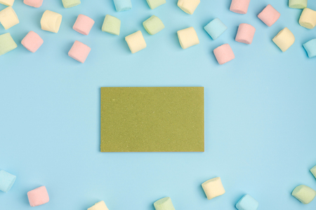 Blue paper background with marshmallow and notepad. Place for your text. Cozy sweet background