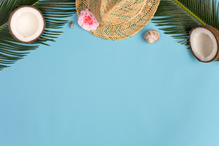 Summer vacation concept. stylish hat, coconuts and green palm leaves on blue background, flat lay. space for text