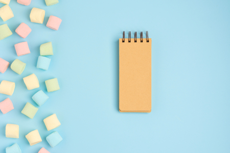 Blue background with marshmallow and blank notepad. Place for your text. Cozy sweet background