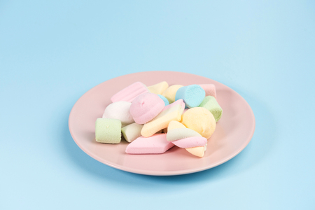 Pink plate with marshmallow isolated on blue background.