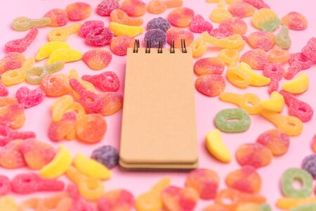 Sugary jellies and blank notepad on pink background. Place for your text. Cozy sweet background