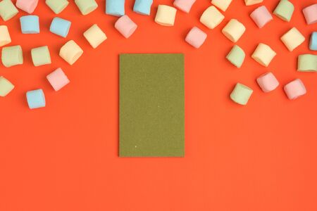 Coral paper background with marshmallow and blank notepad. Place for your text. Cozy sweet background 스톡 콘텐츠