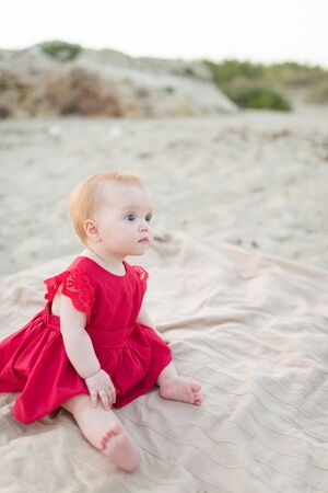 Cute baby girl in a red dress sitting and playing on the beach with sand