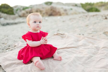 Beautiful little baby girl sitting on the beach