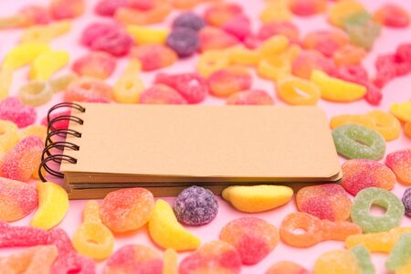 Pink paper background with sugary jellies and blank notepad. Place for your text. Cozy sweet background