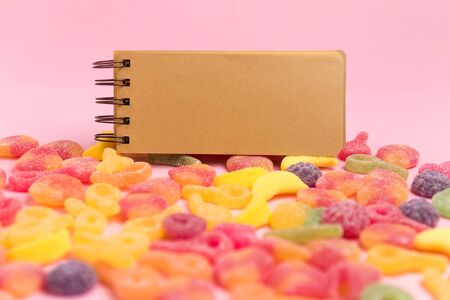 Pink background with sugary jellies and blank notepad. Place for your text. Cozy sweet background 스톡 콘텐츠