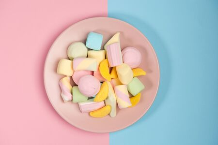 Pink plate with marshmallow, isolated on blue and pink, background. Top view.