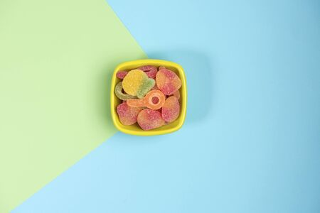 Small bowl with gummy candies isolated on green and blue background. Top view.