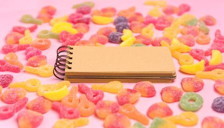 Coral paper background with sweets and blank notepad. Place for your text. Cozy sweet background
