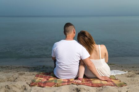 Romantic portrait of couple in love hugs sitting on the beach at the sunset. Against the backdrop of the sea.