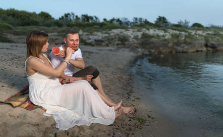 Pregnant couple on the beach, sitting  on the sand and eating watermelon. Archivio Fotografico