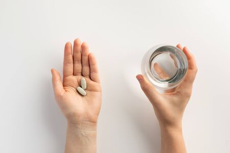 Hands holding a glass of water and pills. Top view. Stock fotó