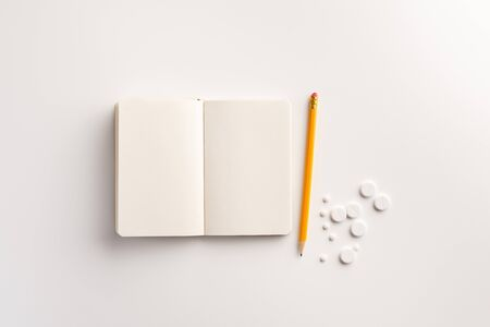 Pills, notepad and pencil on white background. Medical concept. Flat lay. 免版税图像
