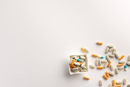 Bowl with scattered pills on white background. Flat lay.