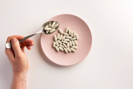 Male hand holding spoon with pills. Plate with pills. Flat lay.