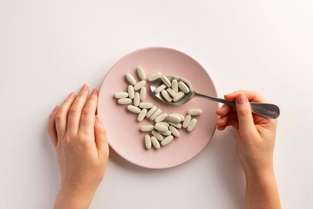 Female hand holding spoon with dietary supplements. Plate with dietary supplements. Flat lay