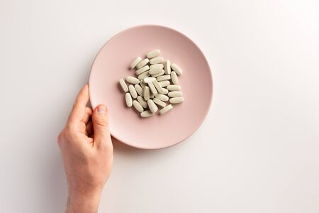 Male hand and plate with dietary supplements. Flat lay. Фото со стока - 131799038