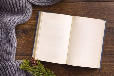 Open book and winter decor, on wooden background. Flat lay, top view, copy space. Banque d'images