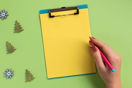 Female hand holding pen, clipboard with yellow sheet and christmas decor, on green background. Flat lay, top view, copy space. Banque d'images