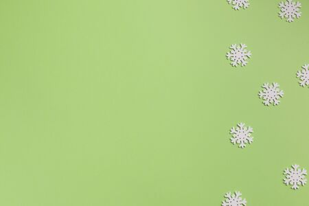 White snowflakes on green background. Christmas, winter concept. Flat lay, top view, copy space.