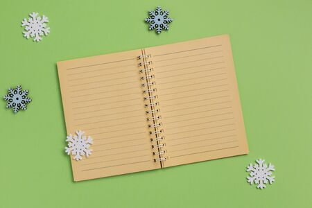 Open notebook and snowflakes, on green background. Flat lay, top view, copy space.