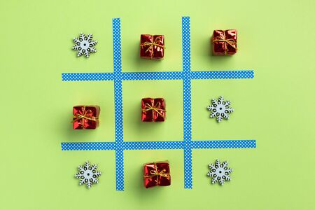 Tic tac toe game with christmas toys, isolated on green background. Christmas, winter concept. Flat lay, top view. Banque d'images