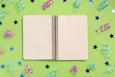 Open notebook, colorful serpentine and stars, on green  background. Flat lay, top view, copy space. Banque d'images