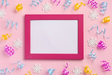 Photo frame, holiday, winter concept. Colorful serpentine and golden stars, on pink  background. Flat lay, top view, copy space.
