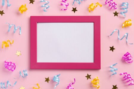 Photo frame, holiday concept. Colorful serpentine and golden stars, on pink  background. Flat lay, top view, copy space.