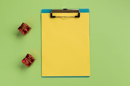 Christmas or New Year planning concept. Clipboard with yellow sheet, on green background. Flat lay, top view, copy space.