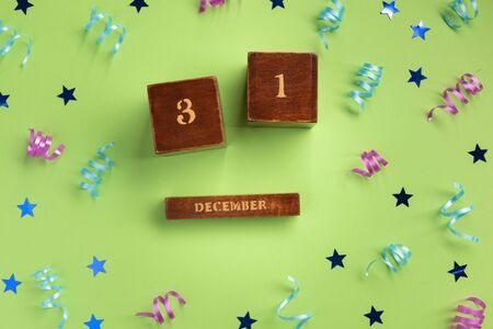 New Year concept. Wooden calendar, colorful serpentine and stars, on green  background. Flat lay, top view, copy space.