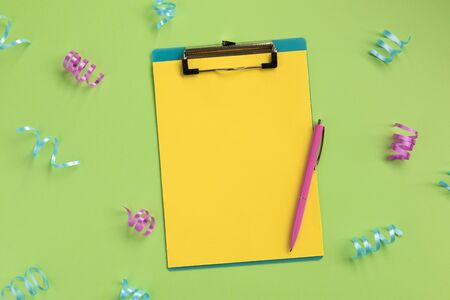 Celebration planning concept. Clipboard, pen, serpentine, on green background. Flat lay, top view, copy space. Banque d'images