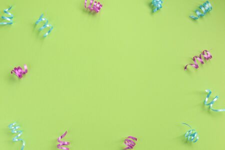 Colorful serpentine  on green  background. Celebration concept .Flat lay, top view, copy space.