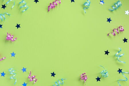 Colorful serpentine and stars, on green  background. Celebration concept .Flat lay, top view, copy space. Banque d'images