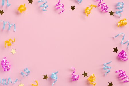 Colorful serpentine and golden stars, on pink  background. Flat lay, top view, copy space.