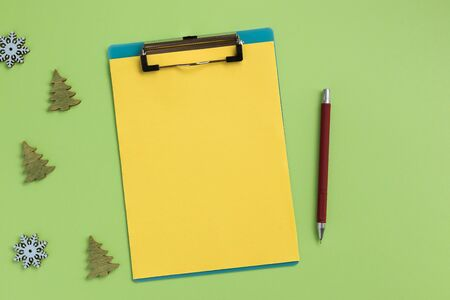 Clipboard with yellow sheet and christmas decor, on green background. Flat lay, top view, copy space. Banque d'images