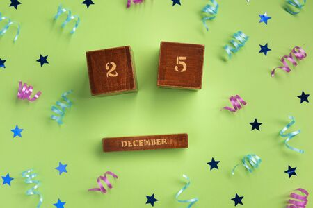 Christmas composition. Wooden calendar, colorful serpentine and stars, on green  background. Flat lay, top view, copy space.
