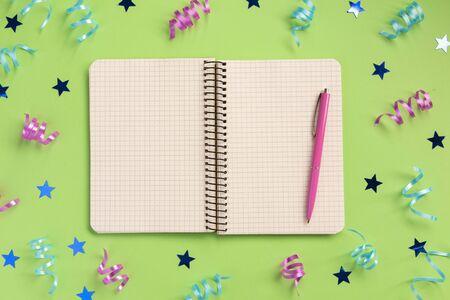 Öffnen Sie Notizbuch, bunte Serpentinen und Sterne, auf grünem Hintergrund. Flache Lage, Ansicht von oben, Kopienraum.