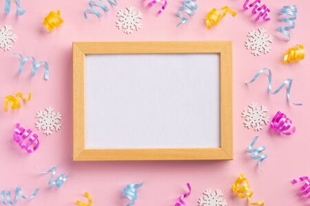 Photo frame. Holiday, winter concept. Colorful serpentine and golden stars, on pink  background. Flat lay, top view, copy space.