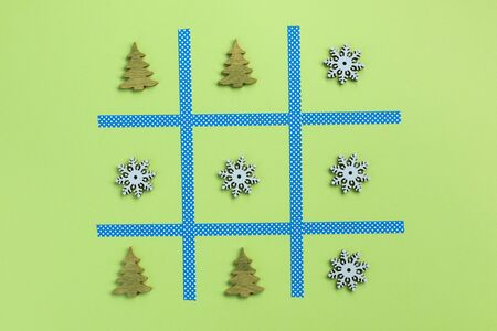 New Year tic tac toe game, isolated on green background. Christmas, winter concept. Flat lay, top view.